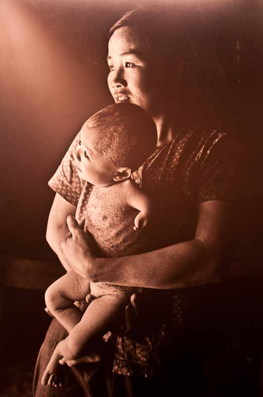 A warm portrait of a mother and her baby deformed by agent orange.