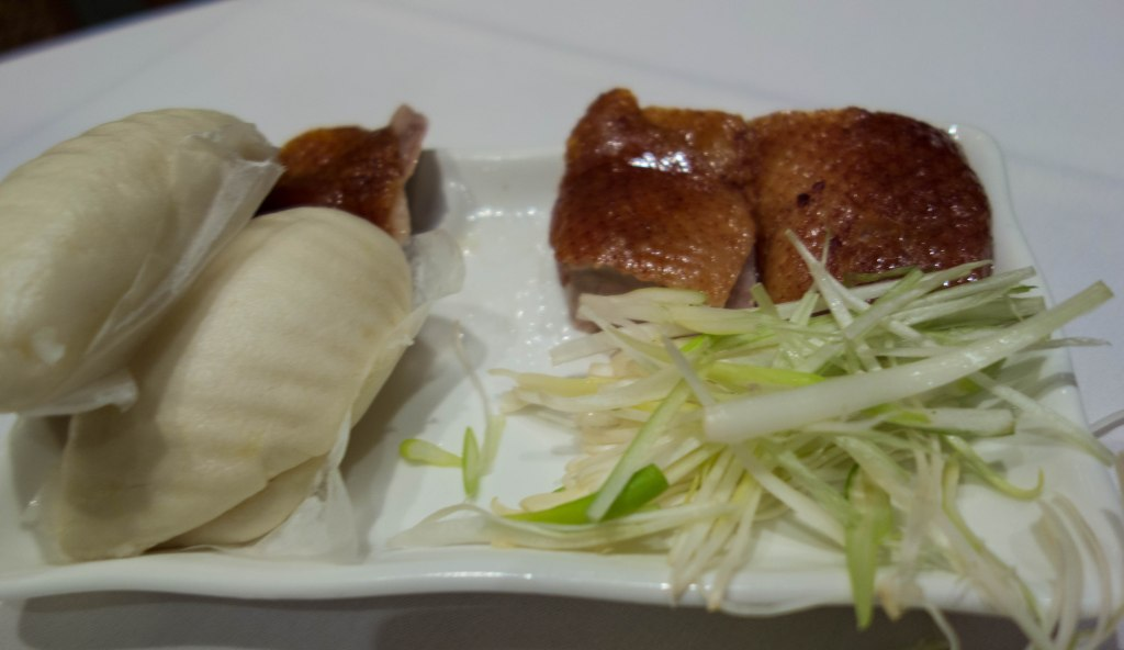 Peking duck--crispy duck, sliced scallions and steamed buns