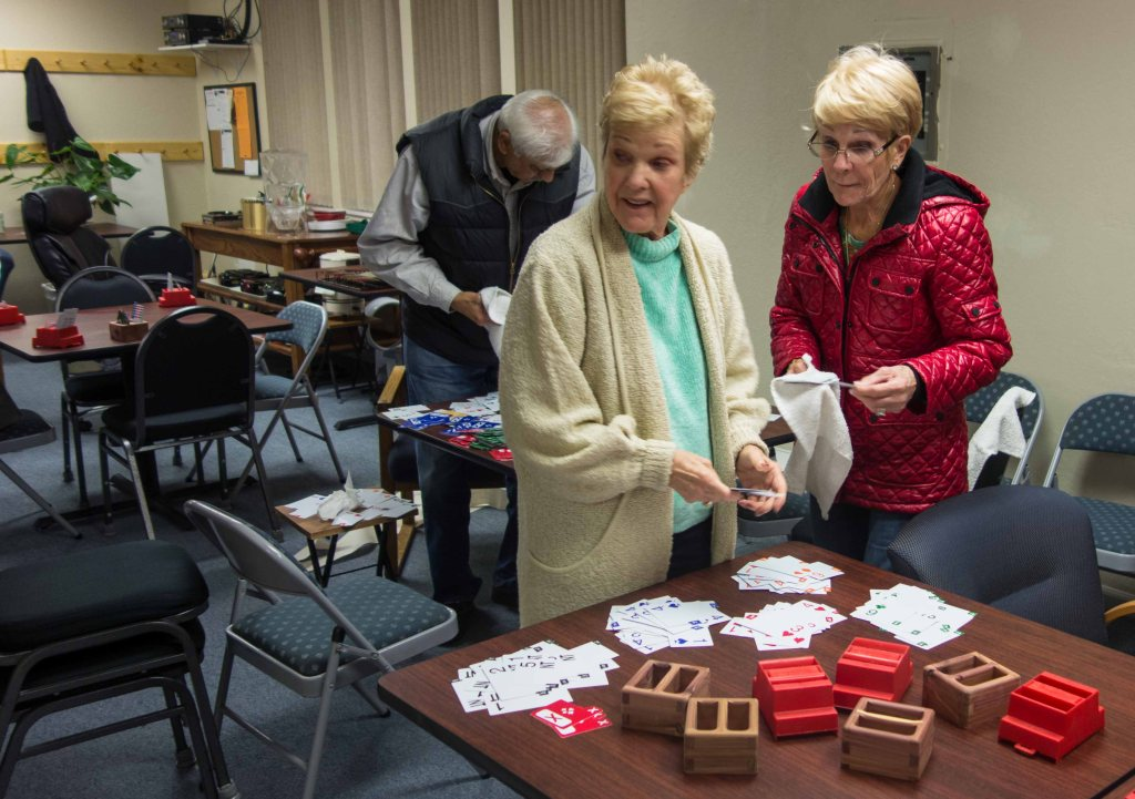 Bonnie Johnson and Kathy Grey putting bidding boxes back together