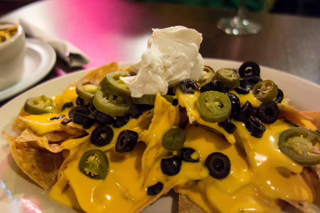 Nachos covered in  melted cheese, topped with jalapenos and sour cream.