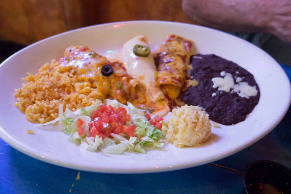 Three enchiladas.  On a plate the size of a manhole cover.