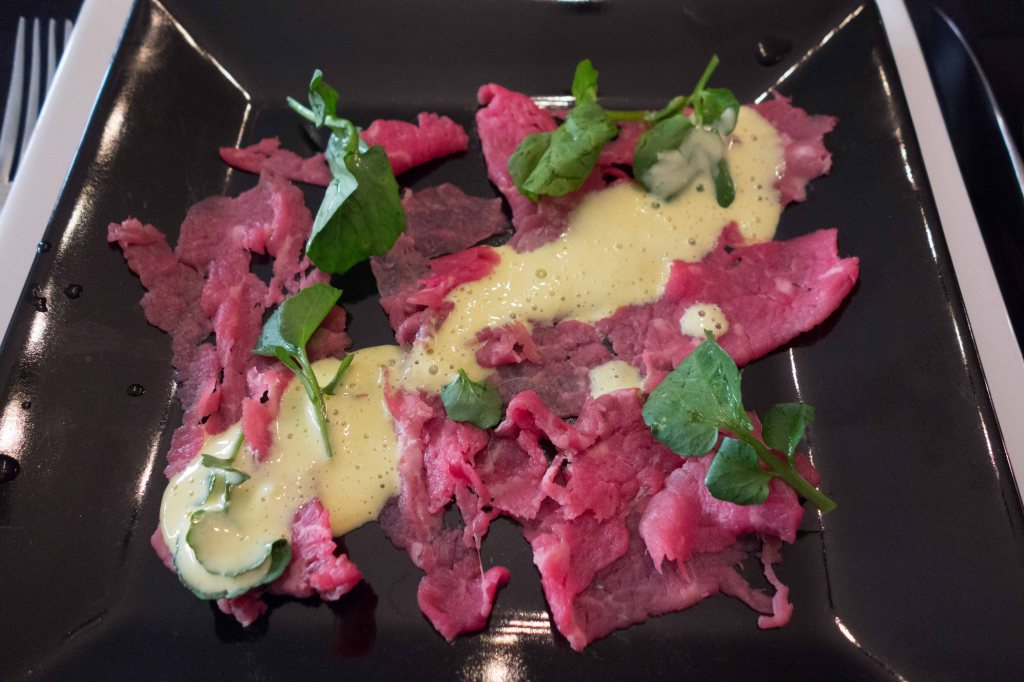 Raw beef, sliced thin and pounded thinner.  Drizzled with a thin aioli.