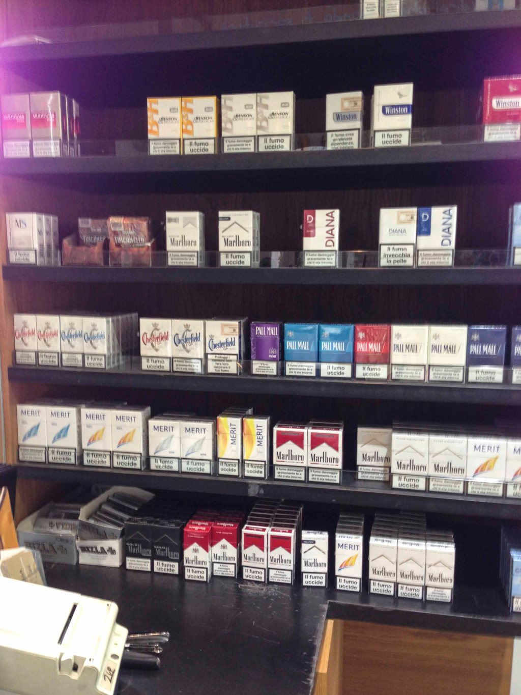A rack of cigarettes behind the counter at a diner.