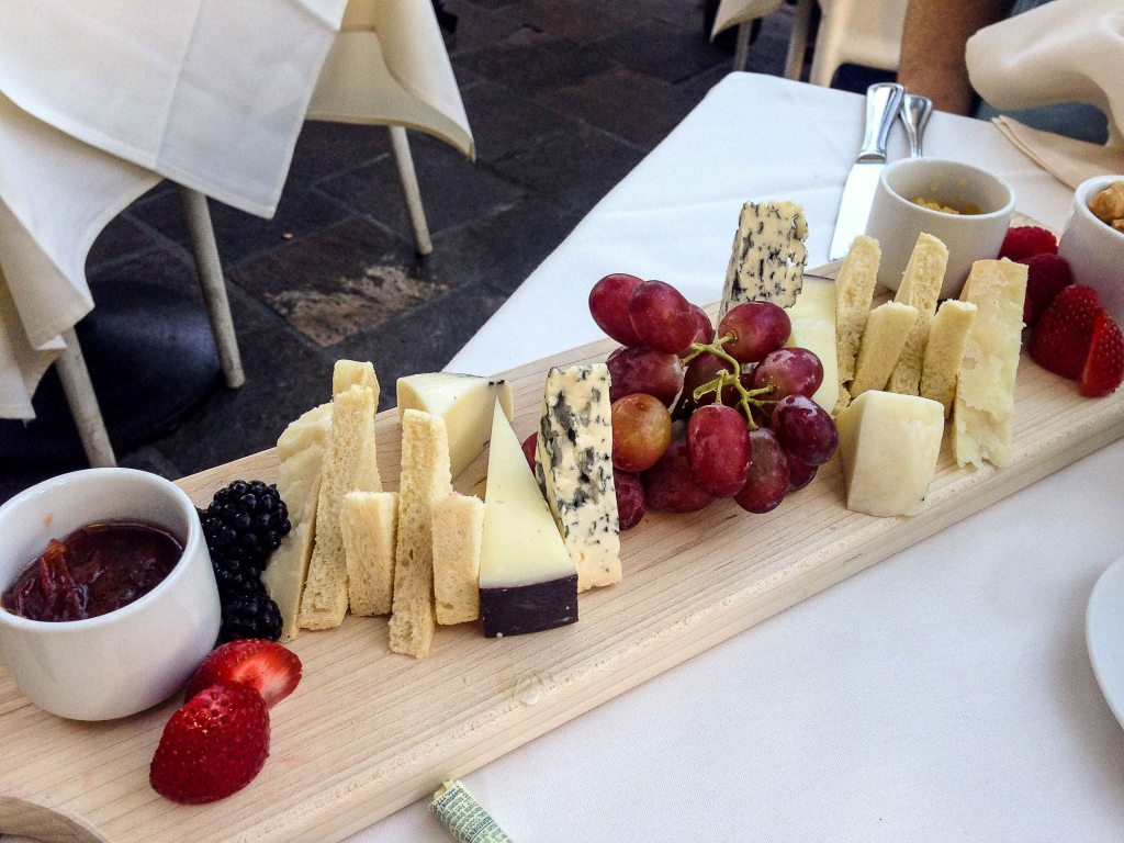Four different Italian cheeses, breads, jams, hazelnuts, grapes, strawberries and blackberries.
