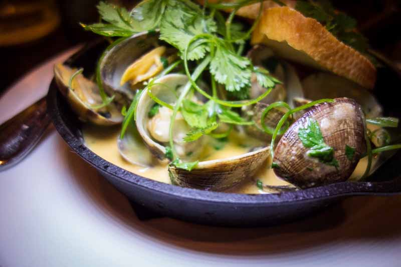 A frying pan full of Manilla clams served in a Thai curry broth
