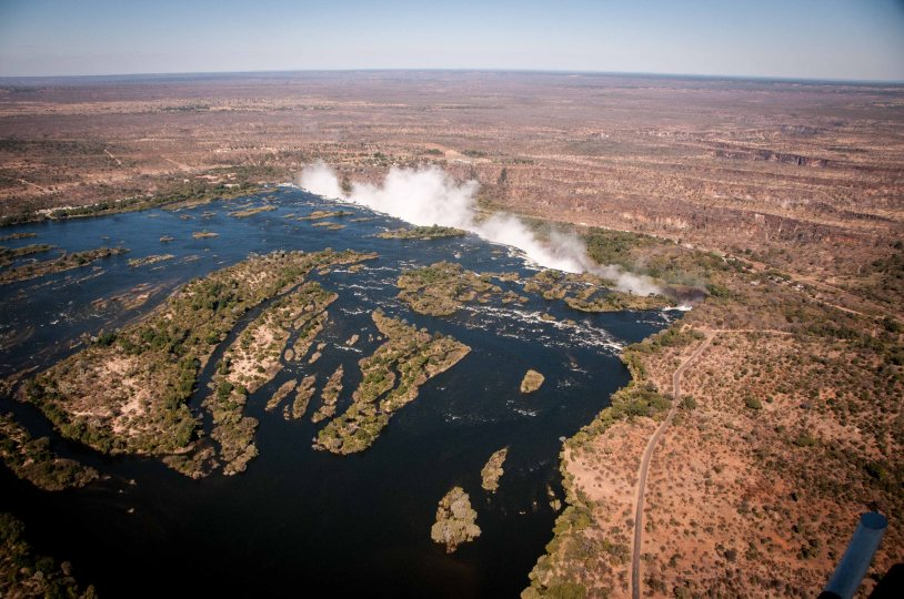 The Zambezi river spreading out over a basalt base in Zambia, leading up to the falls.