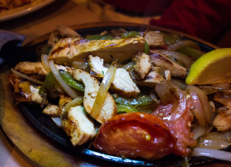 A sizzling plate of chicken, onions and green peppers, the heart of the fajita.