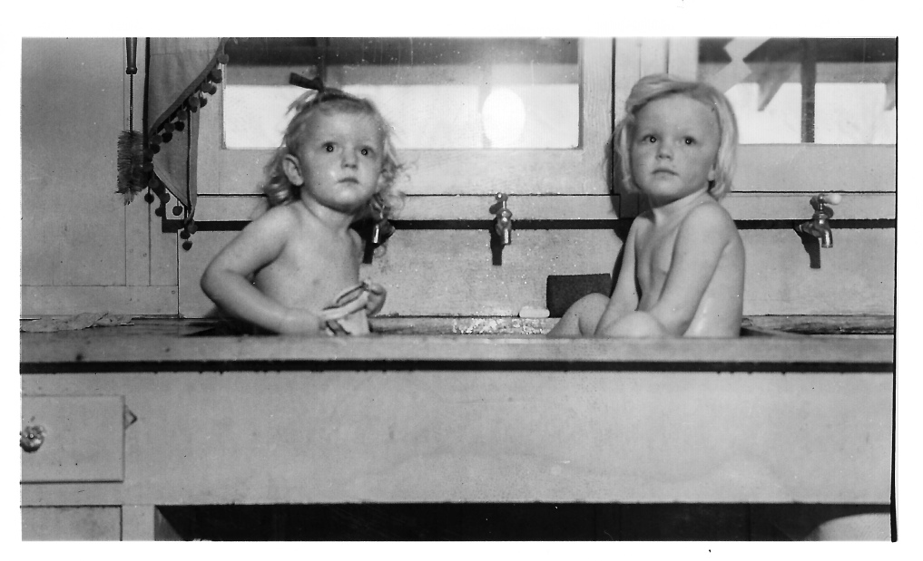 Gail and her sister Susan getting a bath in the kitchen sink.