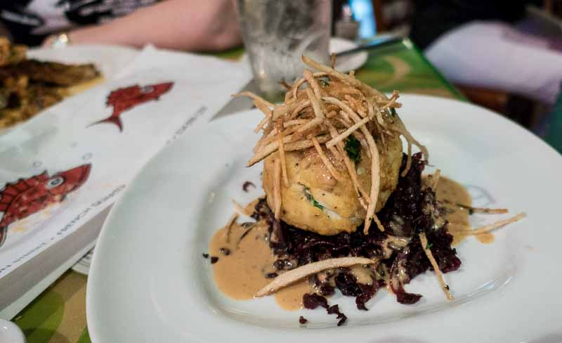 A huge crab cake on red cabbage.