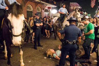 Girl passed out on the street, horse patrol holding back the crowd