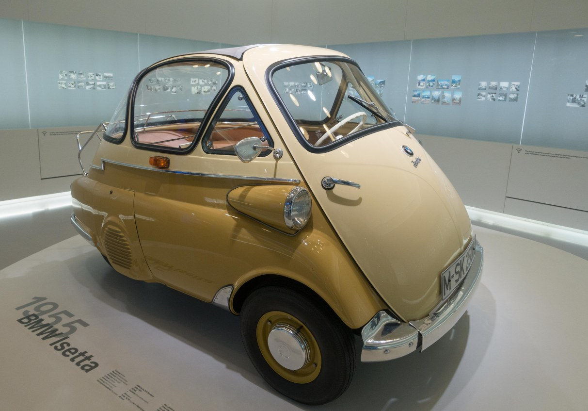 1955 Isetta.  There is only one door--the front of the vehicle opens out, steering wheel and all.