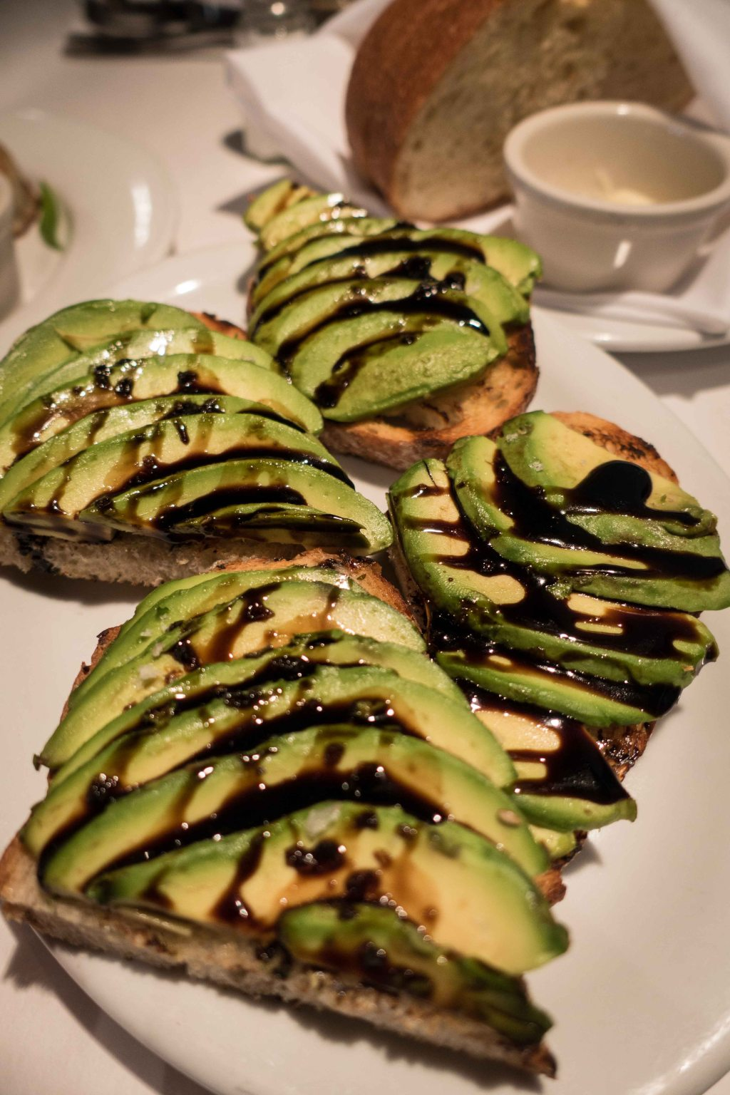 Sliced ripe avocado on toast with balsamic reduction.  Very close to a meal all by itself.