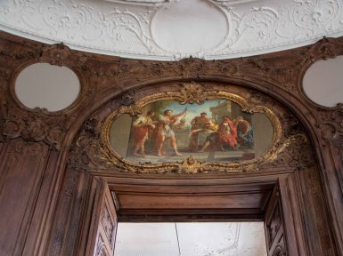Plastered ceilings, intricate woodwork on the wall and oil paintings over the doors.